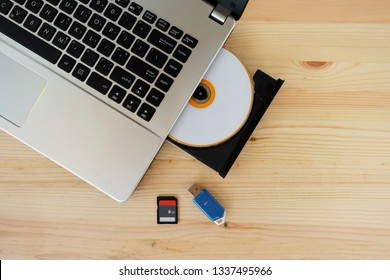 SD Card, Flash Drive USB3.0 and CD DVD Drive Writer Burner Reader of laptop computer on wooden background, Concept of Data storage device