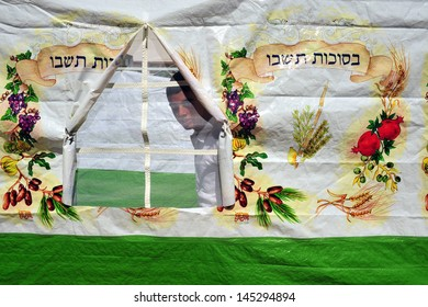 SDEROT, ISR - OCT 10:Israeli man inside a sukkah on Oct 10 2008.Sukkot commemorates the time when the Jews wandered in the desert after the Exodus from Egypt.