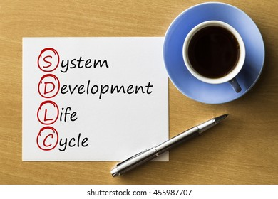 SDLC - System Development Life Cycle - handwriting on notebook with cup of coffee and pen, acronym business concept