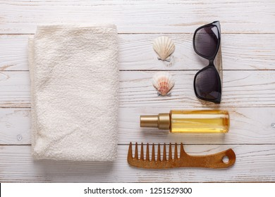 Sea accessories on wooden background Suntan oil, comb, towel, seashells, sunglasses. Top view