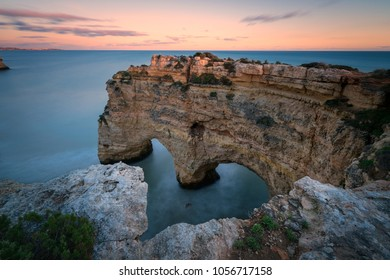 sea arches forming a heart on the Algarve coast at sunset