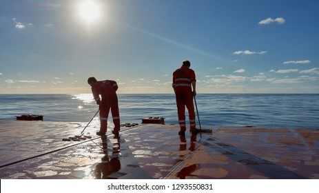 At sea, Atlantic ocean - Circa November 2018: Ships crew members painting hatch cover outdoors onboard of a merchant ship with blue sky on a background. Ship maintenance concept. Teamwork concept.