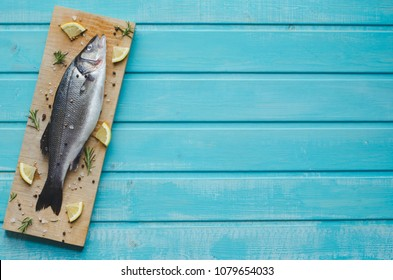 Sea bass on kitchen table with lemon and rosemary on blue wooden background. Top view with space to write.