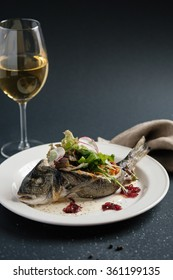 Sea bass in a plate with white wine and napkin. Vertical.