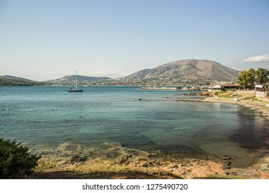 sea bay near city port with small yacht on water surface and mountain background landscape in bright vivid summer clear weather time