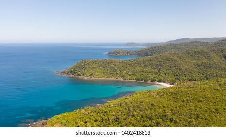 Sea bay with turquoise water and a small white beach.Coast of the island of Camiguin, Philippines.Beautiful lagoon and volcanic island covered with dense forest, view from above.