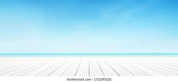 Fondo de playa de mar con parqué blanco en primer plano. Paisaje en el cielo azul de las nubes.