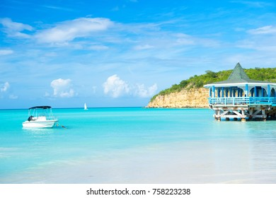 Sea beach with boat and wooden shelter on turquoise water in st johns, antigua on blue sky background. Summer vacation on caribbean. Adventure, travelling, wanderlust concept