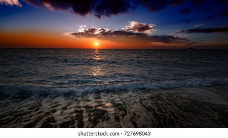 sea and beach during sunset with a colorful horizon and traveling clouds