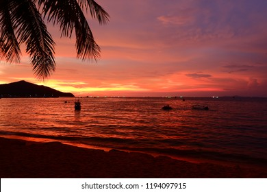 Sea and beach in the evening. The sun, orange and red reflect on the sea.