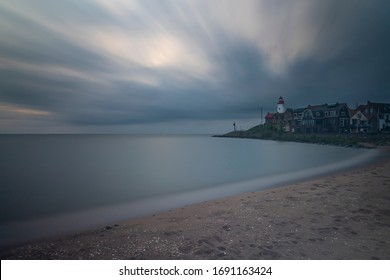 Sea and beach at the lighthouse in Urk in Holland. Photo for a long time in blue watch time. There are dynamic clouds floating in the sky at dusk.
