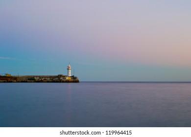 Sea beacon in port, evening.