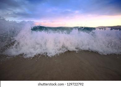 sea big wave against sunset