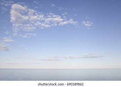 Sea with blue water, sky and clouds. Sunset above seascape