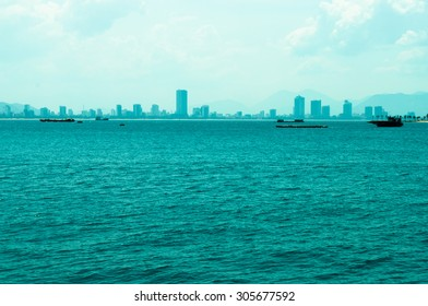 Sea with boat and city on the horizon