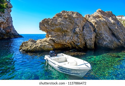 Sea boat at lagoon cliff view. White sea boat on sea water rock. Sea boat lagoon scene
