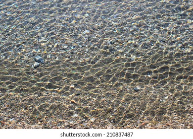 Sea bottom with pebbles through clear water