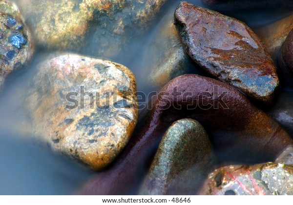 The sea breaks over the pebbles. Exposure time has produced the misty effect of the water.