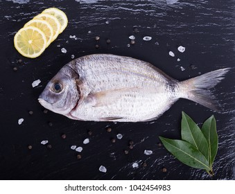Sea bream with bay leaves, lemon slices, pepper corns and rock salt on a slate board.