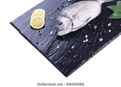 Sea bream with bay leaves, lemon slices, pepper corns and rock salt on a slate board isolated on a white background