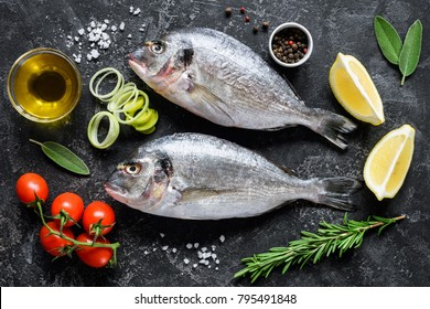 Sea bream or dorado sea fish, olive oil, spices herbs and cooking ingredients on dark slate background. Top view. Mediterranean cuisine, healthy eating, healthy cooking concept