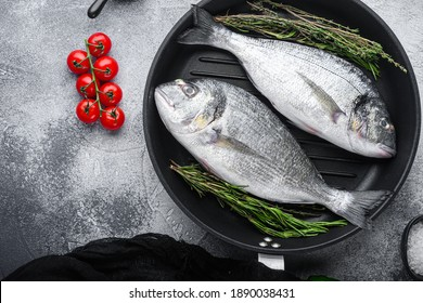 Sea bream or dorado raw fish on grill pan with ingredients on grey white textured background, top view space for text