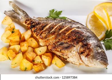 Sea bream fish with potato on white plate close-up