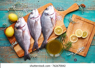 Sea bream with lemon rosemary and marinade on blue wood background