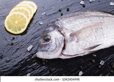 Sea bream with lemon slices, pepper corns and rock salt on a slate board.