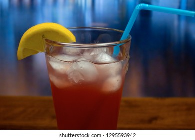 Sea Breeze cocktail in highball glass with with ice and slice of lemon