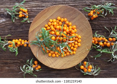 Sea buckthorn background. Organic ripe sea buckthorn on old wooden plate, rustic background. Top view