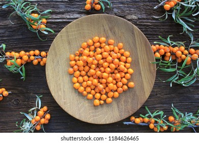 Sea buckthorn background. Organic ripe sea buckthorn on old wooden plate, rustic background. Top view .
