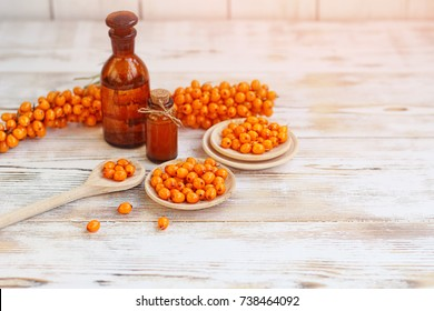 sea buckthorn berry and bottles of sea buckthorn oil on wooden table. useful natural organic product, medical treatment.