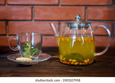 Sea buckthorn and mint tea in a transparent glass teapot. Close-up, selective focus