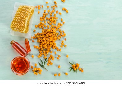 Sea buckthorn, Sea buckthorn oil in glass bottles , honey on blue table. top view