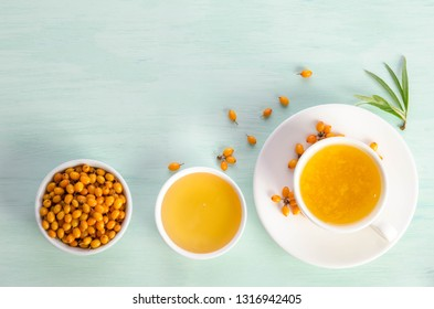 Sea buckthorn in porcelain bowl, honey and cup of  tea with Sea buckthorn on blue table. top view