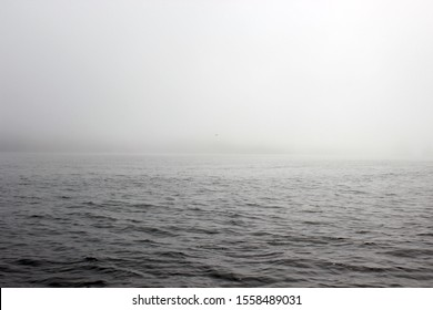 Sea calm in foggy weather on the background of the peninsula