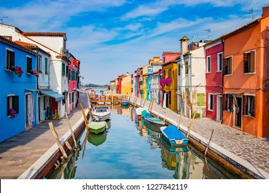 A sea canal with boats in the center of Burano near Venice in Italy. There are many coloful houses.