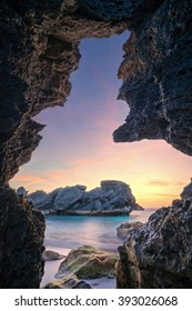 sea cave framing a beautiful beach at sunrise