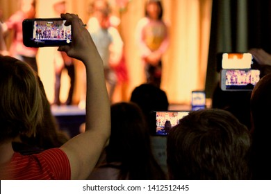 A sea of parents' cell phones are held high to record their children's performance in a school play.