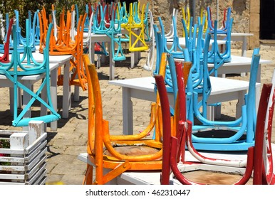 sea city street with colorful chairs and tables
