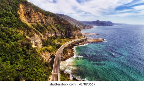 Sea cliff bridge at the edge of steep sandstone cliff on the Grand Pacific drive along pacific coast of Australia, NSW. Aerial view towards distant hill ranges on sunny summer day.