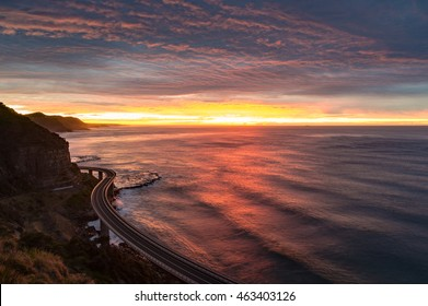 Sea Cliff Bridge on sunrise with beautiful dramatic sky and ocean shore on the background. The Bridge is part of highway Grand Pacific Drive scenic route. NSW, Australia