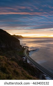 Sea Cliff Bridge on sunrise with moving traffic and dramatic beautiful sky and ocean shore on the background