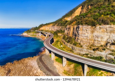 Sea cliff bridge section of the Grand Pacific drive around steep sandstone cliff at the edge of Pacific coast on a sunny day against blue sky in elevated aerial view.