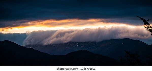 Sea of clouds flowing above mountains at sunset