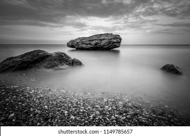 Sea coast with big stones in the water on long exposure. Dramatic black and white seascape.
