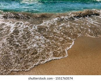 Sea coast, blue sea wave close-up and yellow sandy beach. Montenegro, Adritica, Balkans.
