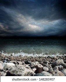 sea coast, stones, waves and dark dramatic stormy sky landscape - shallow DOF