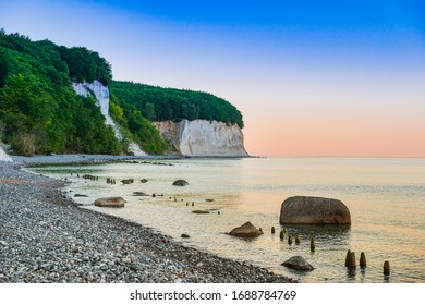 Sea coast and white cliffs on Rugen Island. Wooden breakwater on the beach. Dusk.